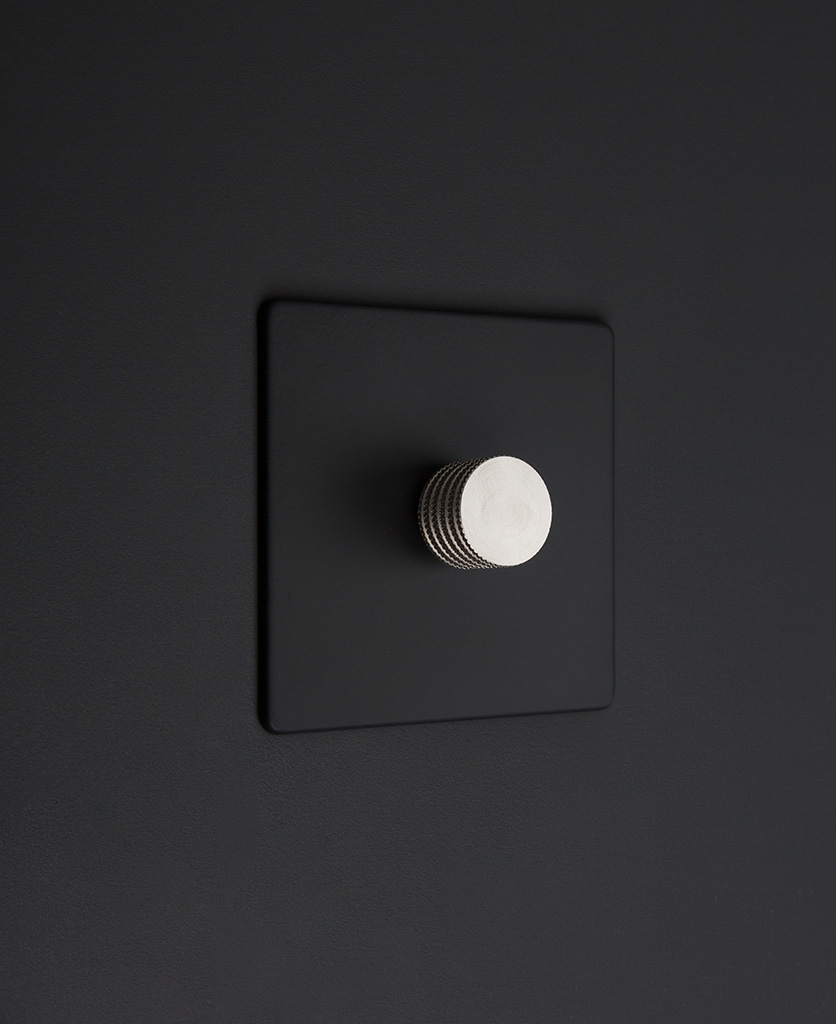 Black one gang dimmer switch with silver knobs on black background