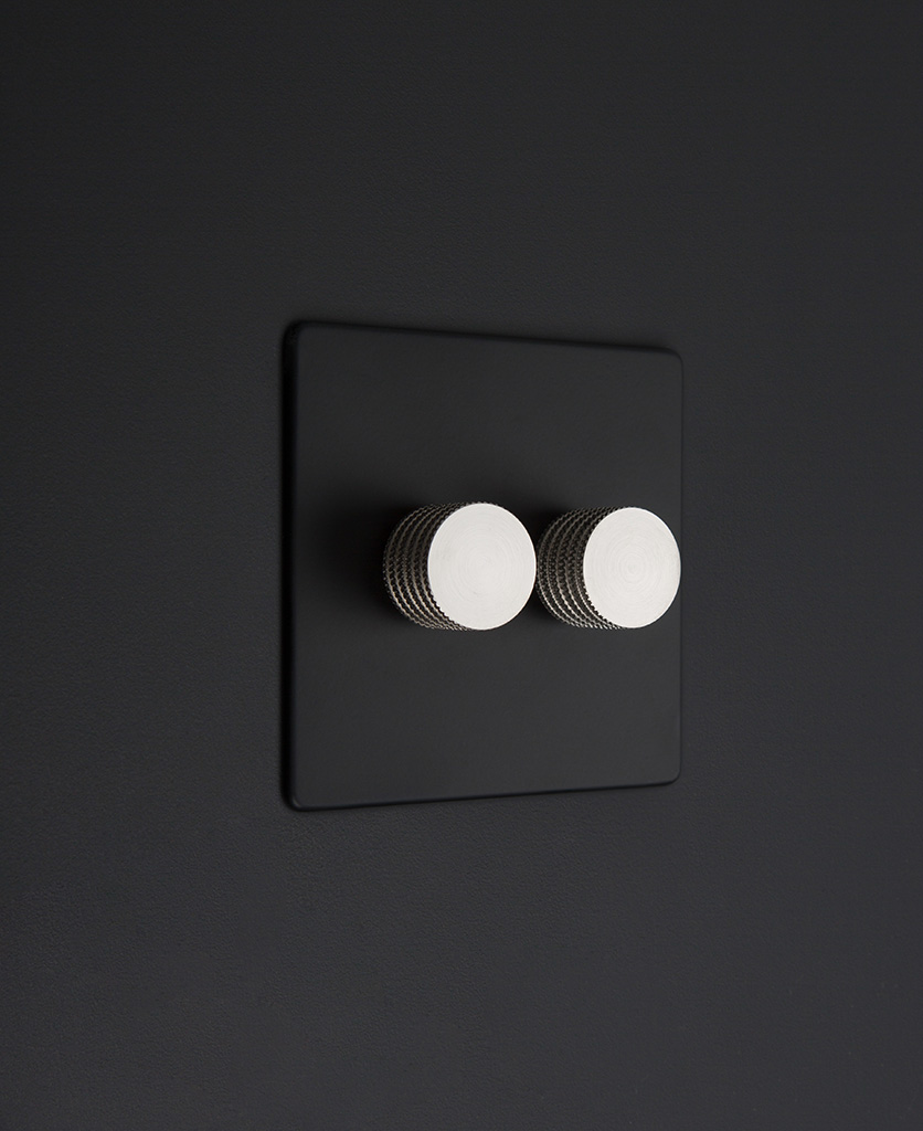 Black standard two gang dimmer switch with silver knobs on black background