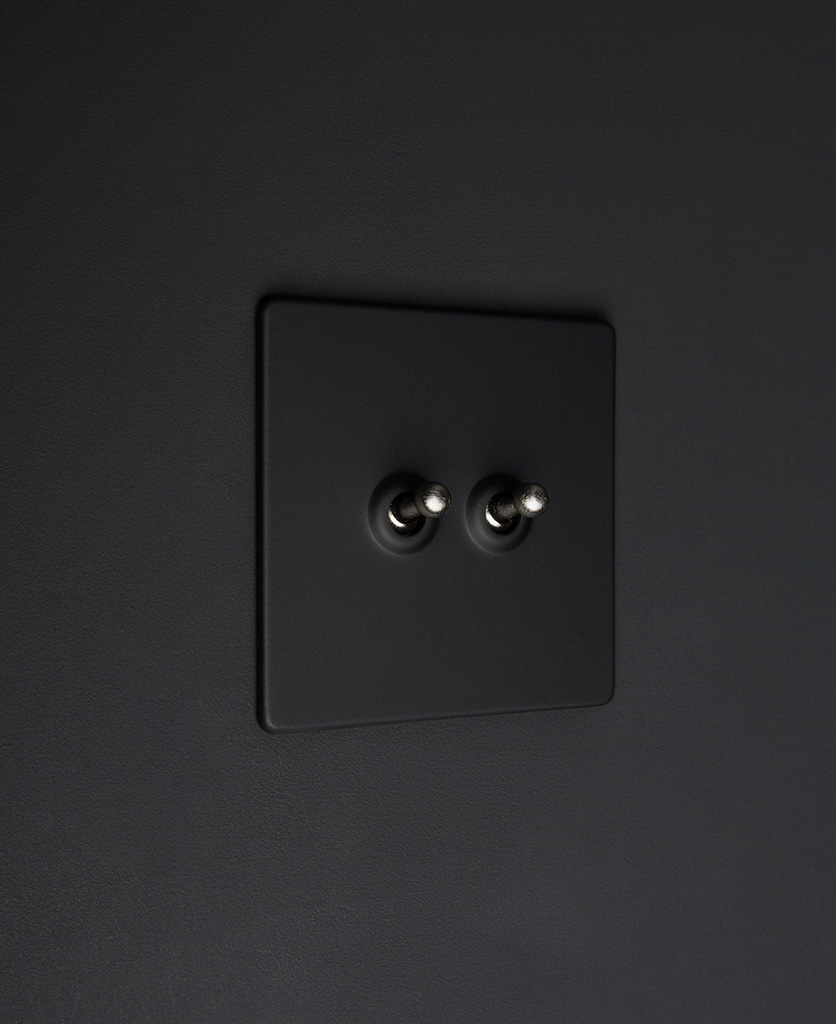 Black two gang toggle switch with silver toggles on black background