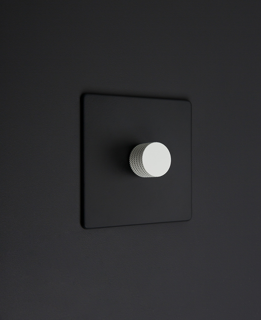 Black one gang dimmer switch with white knobs on black background