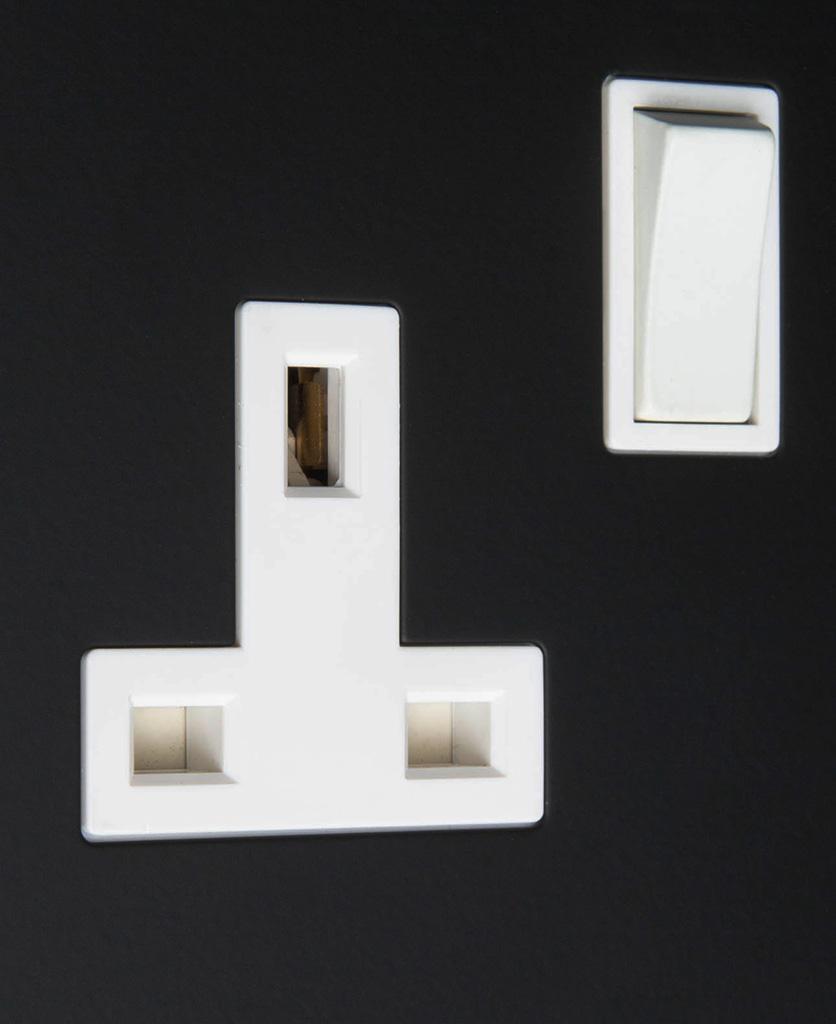 black and white 1g single plug socket on black background close up