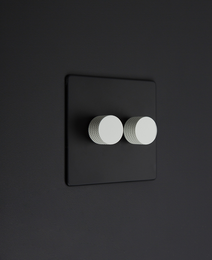 Black standard two gang dimmer switch with white knobs on black background
