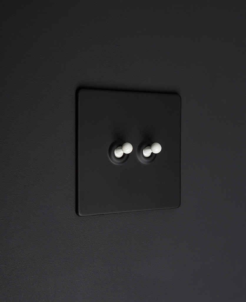 Black two gang toggle switch with white toggles on black background