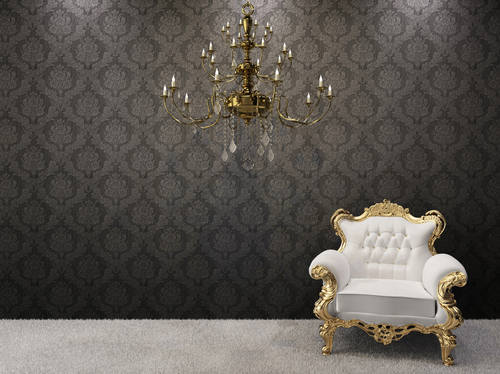 ornate black wallpaper with grand gold and white armchair and gold chandelier