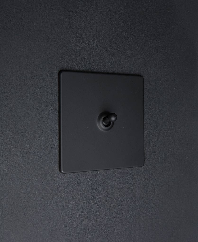 black toggle switch with black toggle detail against black wall