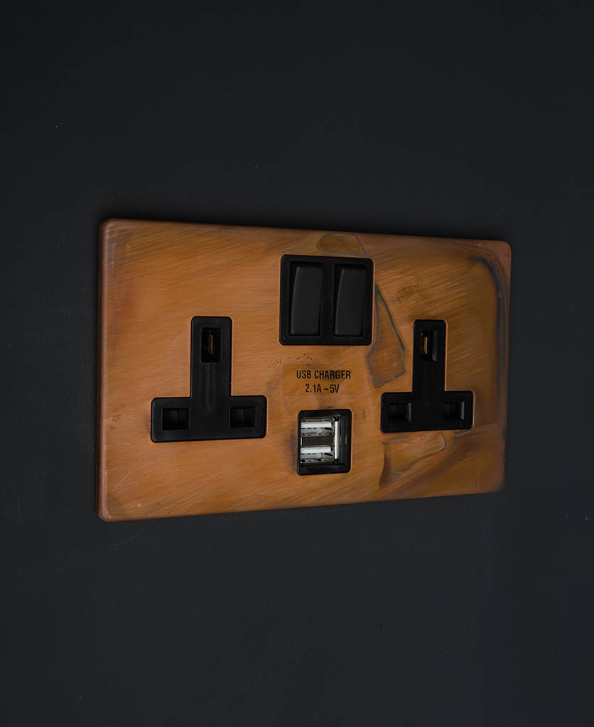 copper & black double usb plug socket with black inserts against black wall