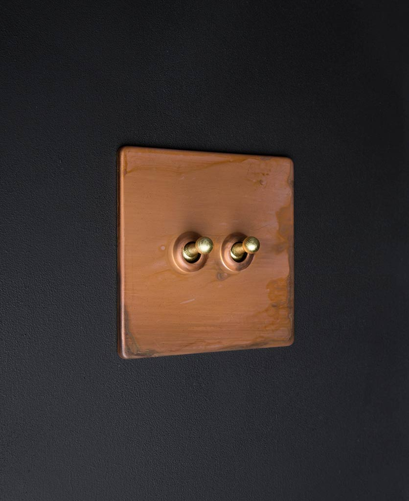 Copper luxury light switches with double gold toggle detail against black background