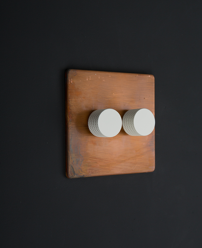 copper & white double dimmer standard against black background