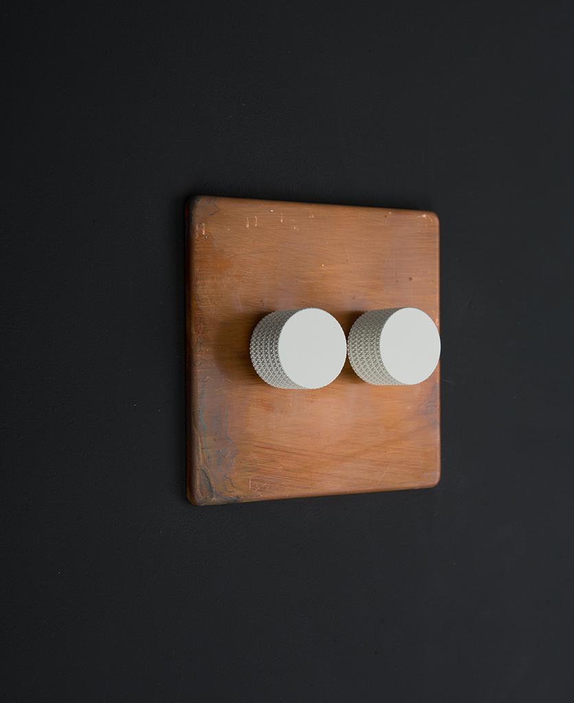copper & white double dimmer standard against black background