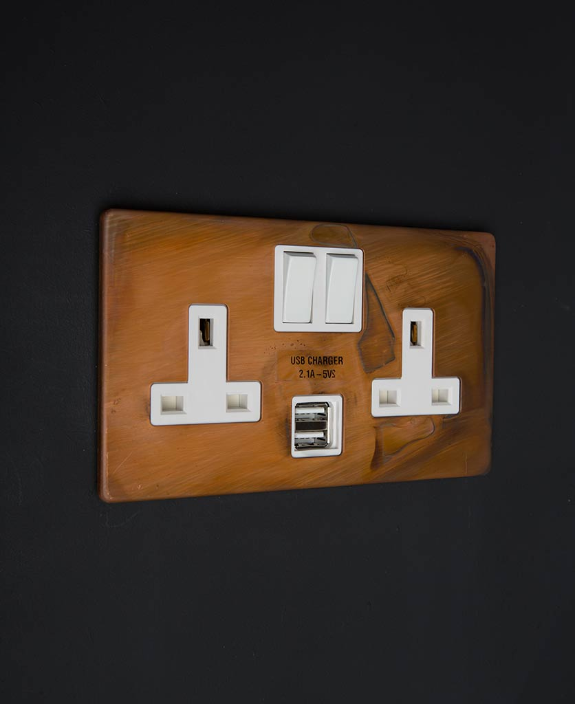copper & black double usb plug socket with white inserts against black wall