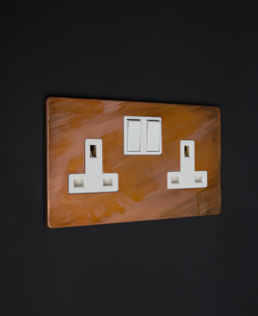 copper double socket with white inserts against black wall