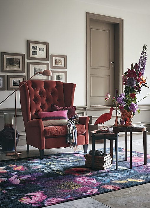 white living room soft brown painted woodwork, red velvet armchair and floral rug