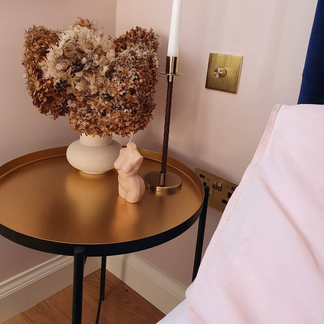 GOLD single dimmer switch on soft pink wall in between a bed and bedside table holding some dried flowers and a candle