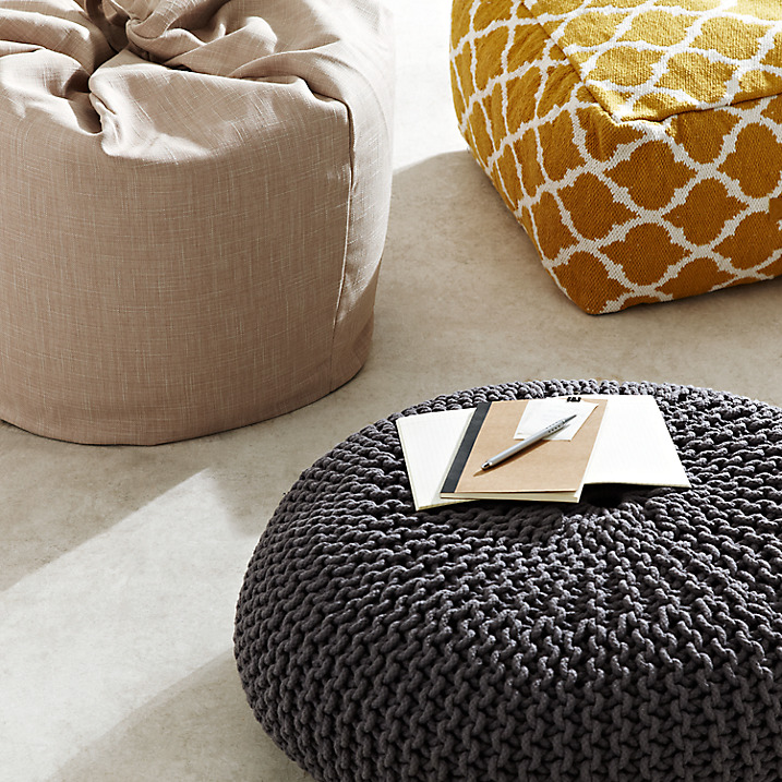grey chunky knitted footstool, yellow patterned stool and beige beanbag on neutral carpet