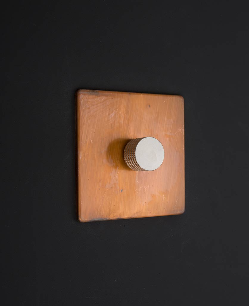 copper two way dimmer switch with silver knurled dimming knob against black background