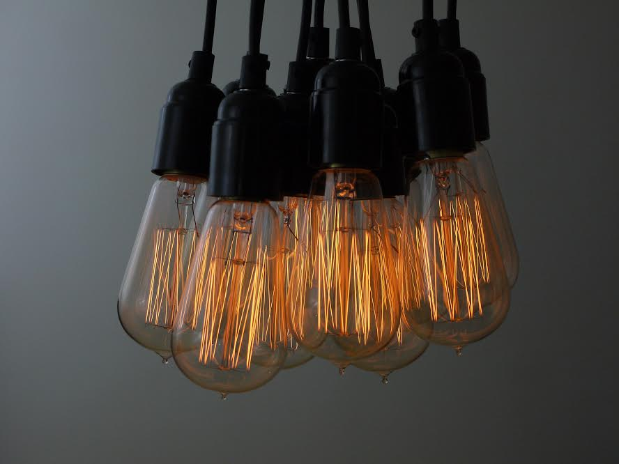 squirrel cage filament bulbs suspended from black bakelite bulb holders against grey background