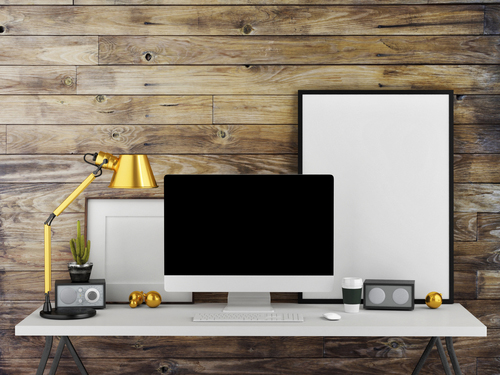 white desk with white computer and brass lamp against wooden panelled wall