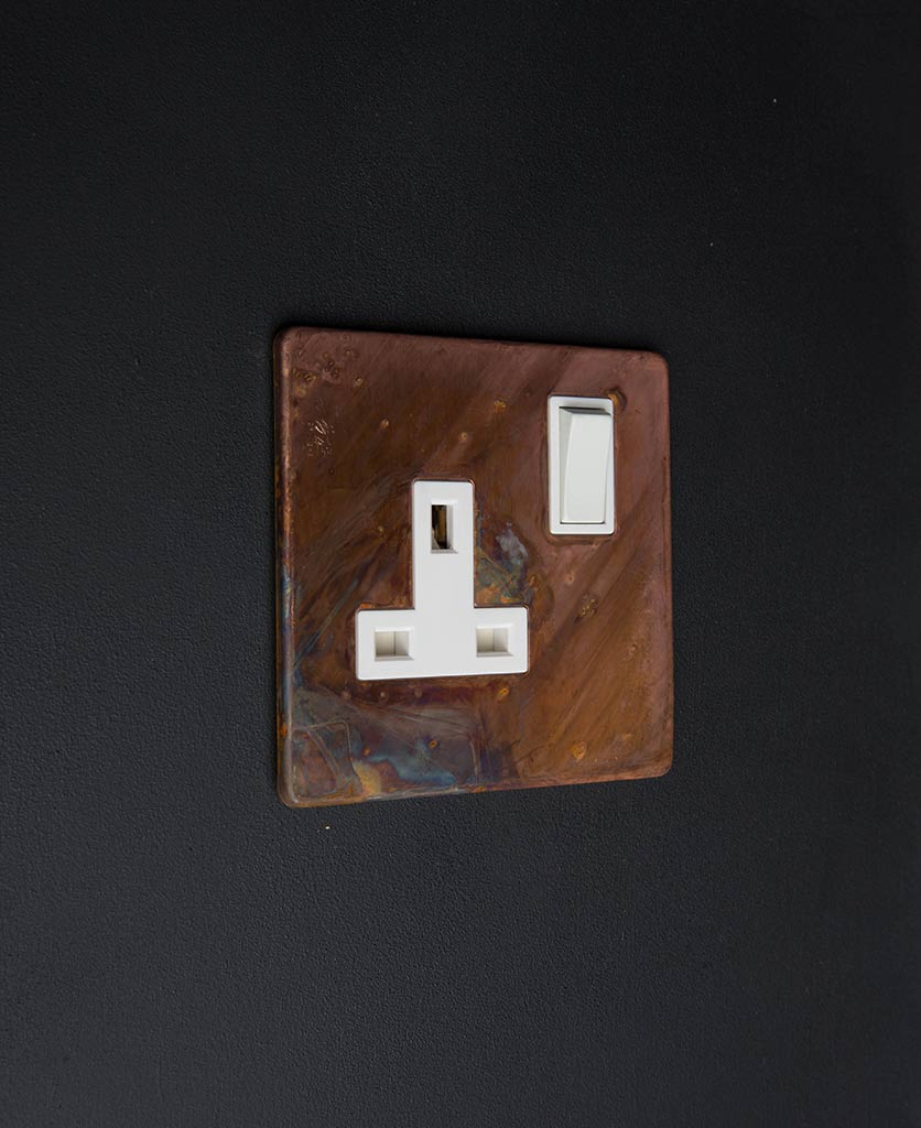 tarnished copper plug sockets with white inserts against black wall