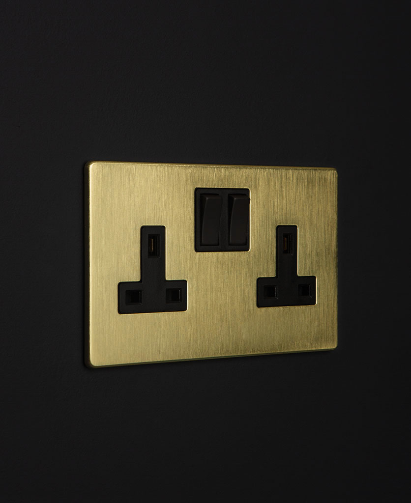 gold & black double plug socket against a black wall