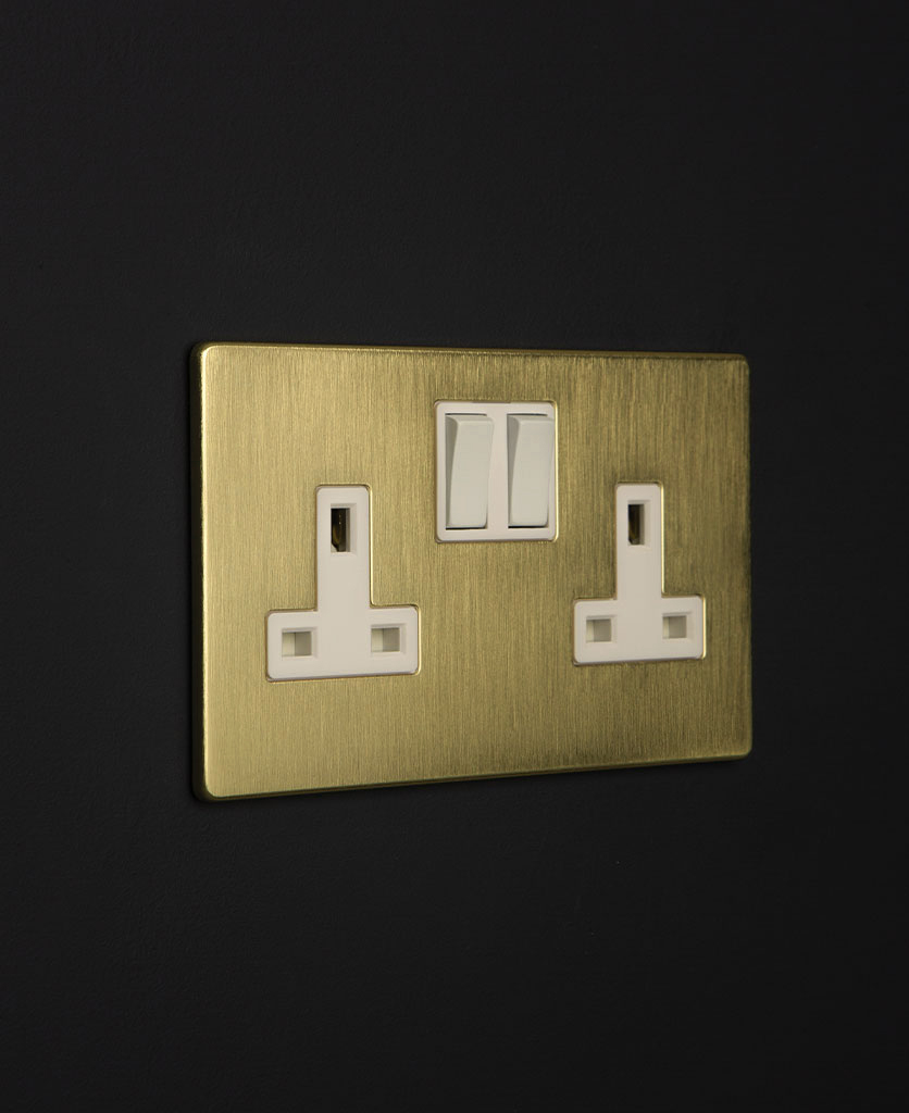 gold & white double plug socket against a black wall