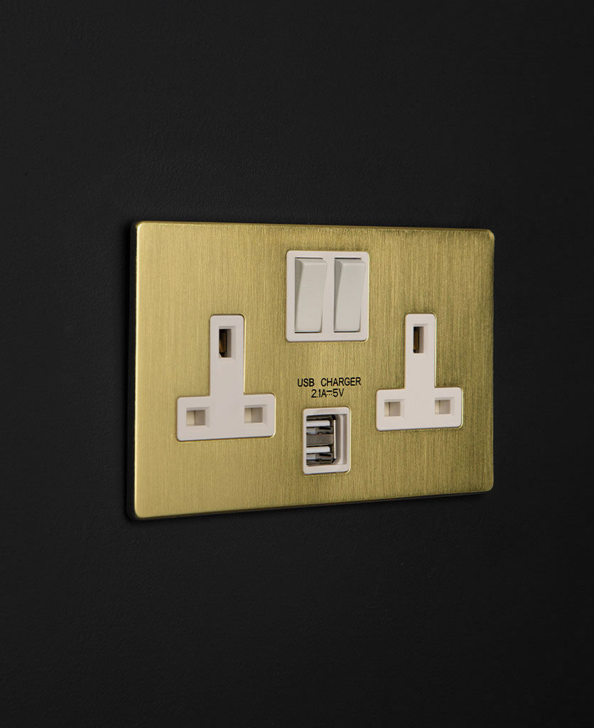 gold & white double socket with USB port and black inserts against a black wall