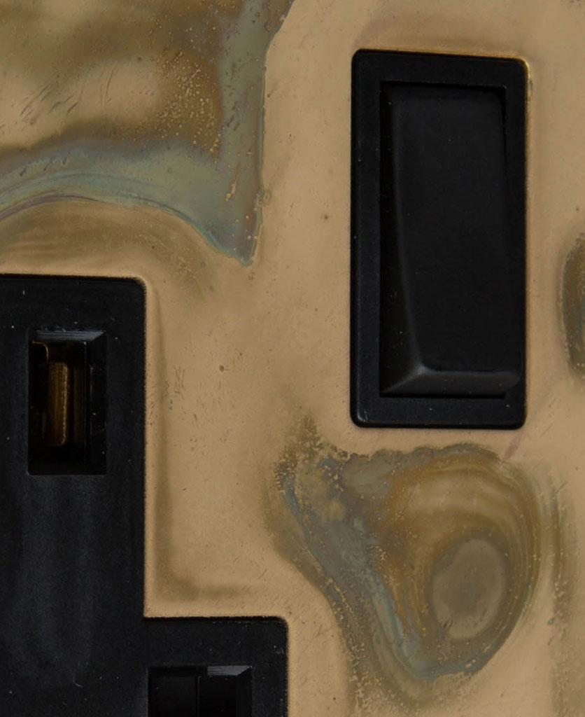 smoked gold and black single plug socket close up