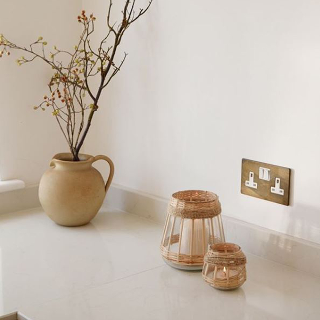 smoked gold and white double socket on white wall in a kitchen