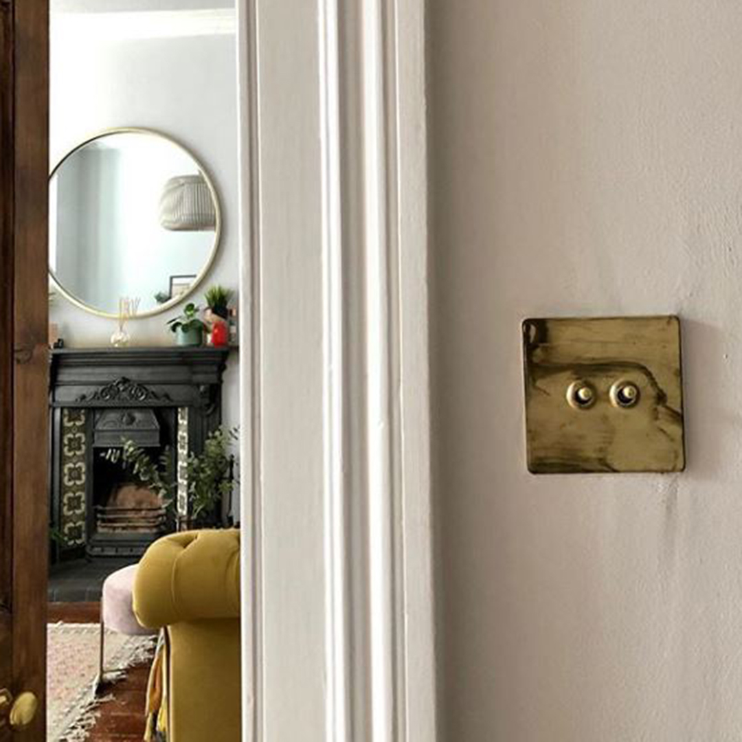 smoked gold and gold double toggle switch besides a doorway
