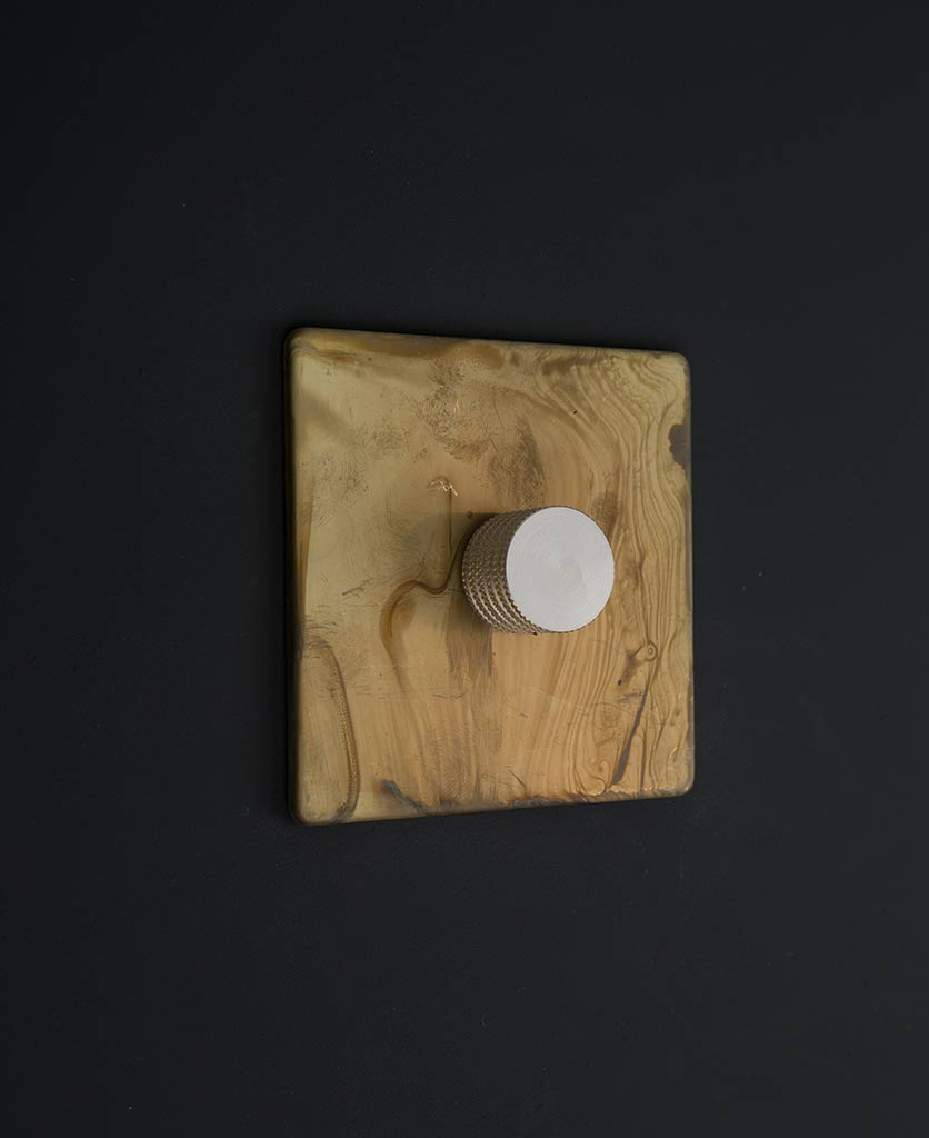 LED Dimmer switch with smoked gold plate and gold dimming knobs against black wall