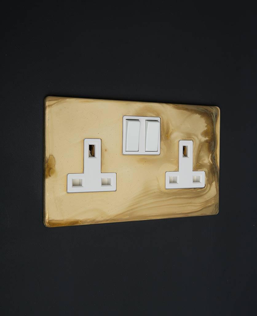 smoked gold & white multi plug socket on black background