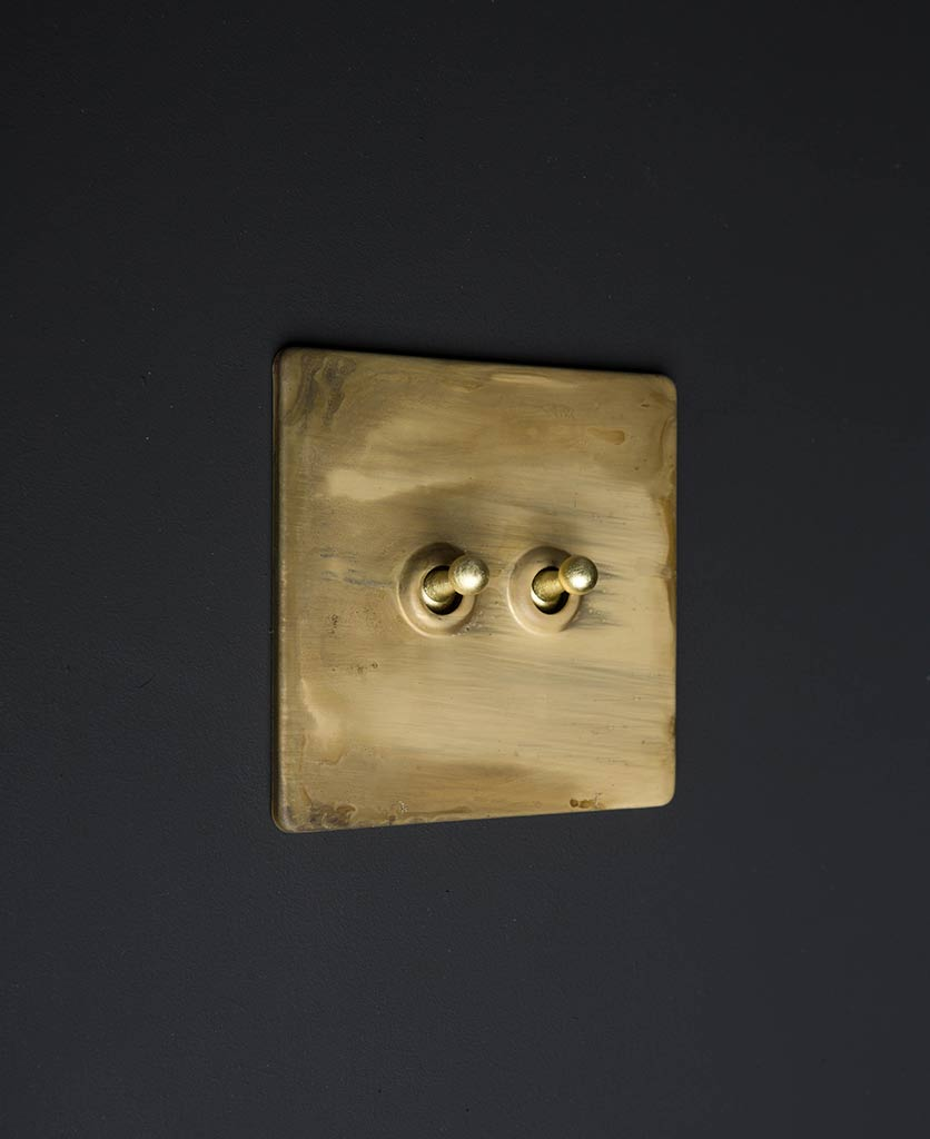 Smoked gold toggle switches with gold double toggle detail against black background