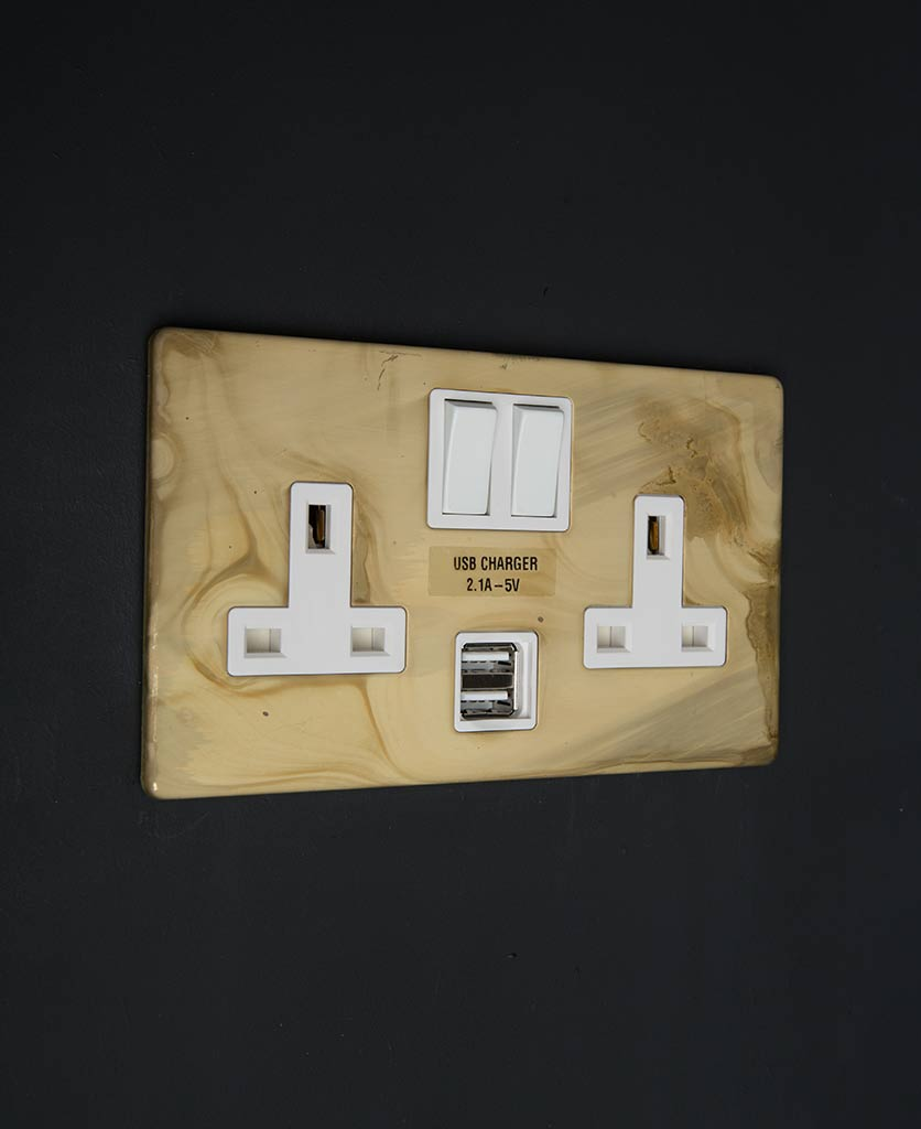 smoked gold & white plug sockets with USB against black wall