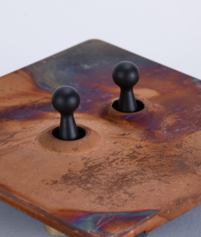 closeup of copper and black double toggle switch against white background