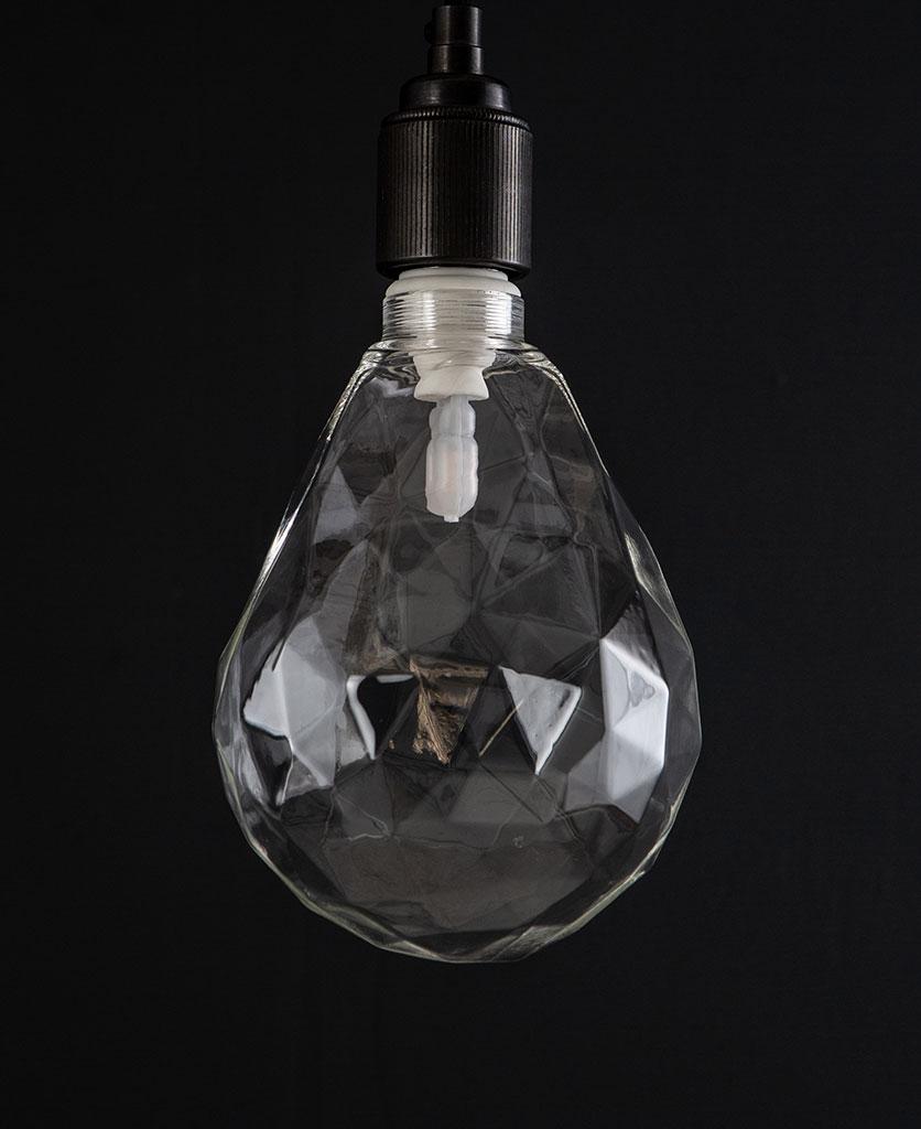 unlit pear geometric e27 led bulb clear pear shaped bulb against black wall