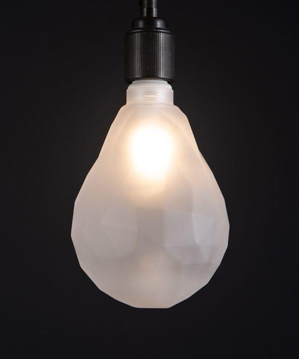 lit pear geometric e27 led bulb frosted pear shaped bulb against black wall