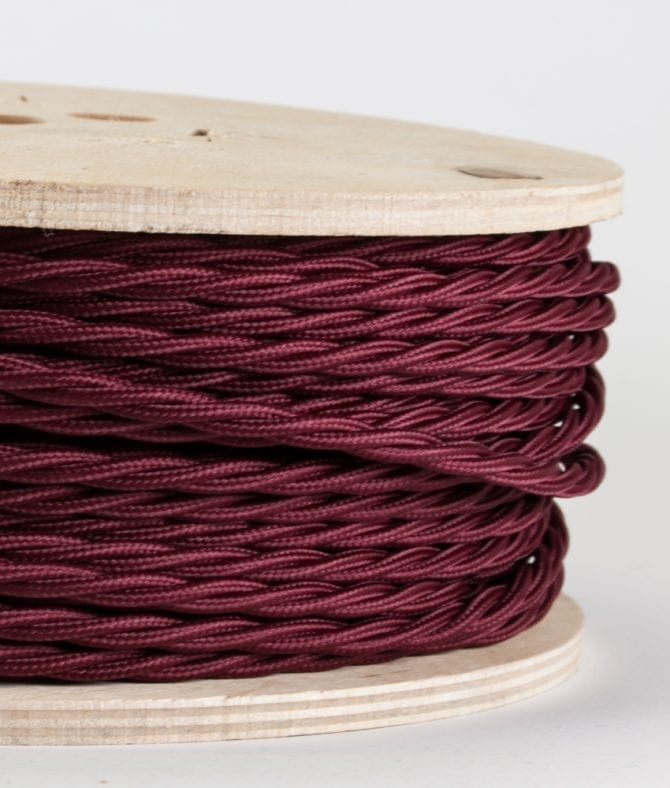 closeup of burgundy twisted cable on reel against white background