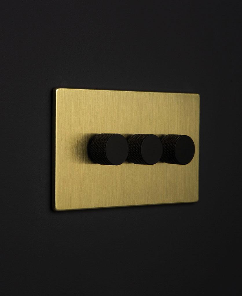 gold & black triple dimmer against black background
