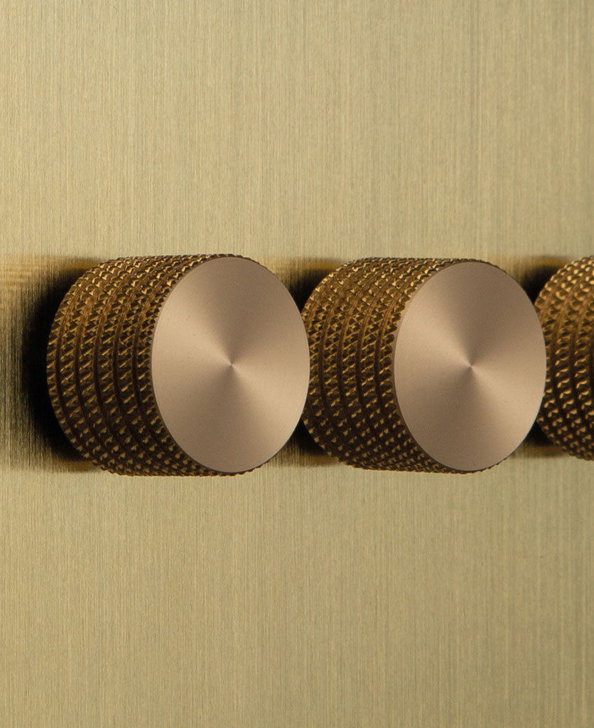 closeup of gold reiple dimmer switch with gold knurled knobs