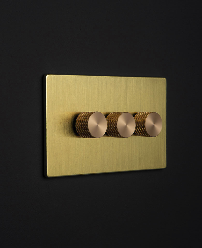 gold backplate with three brass knurled dimmers against black wall