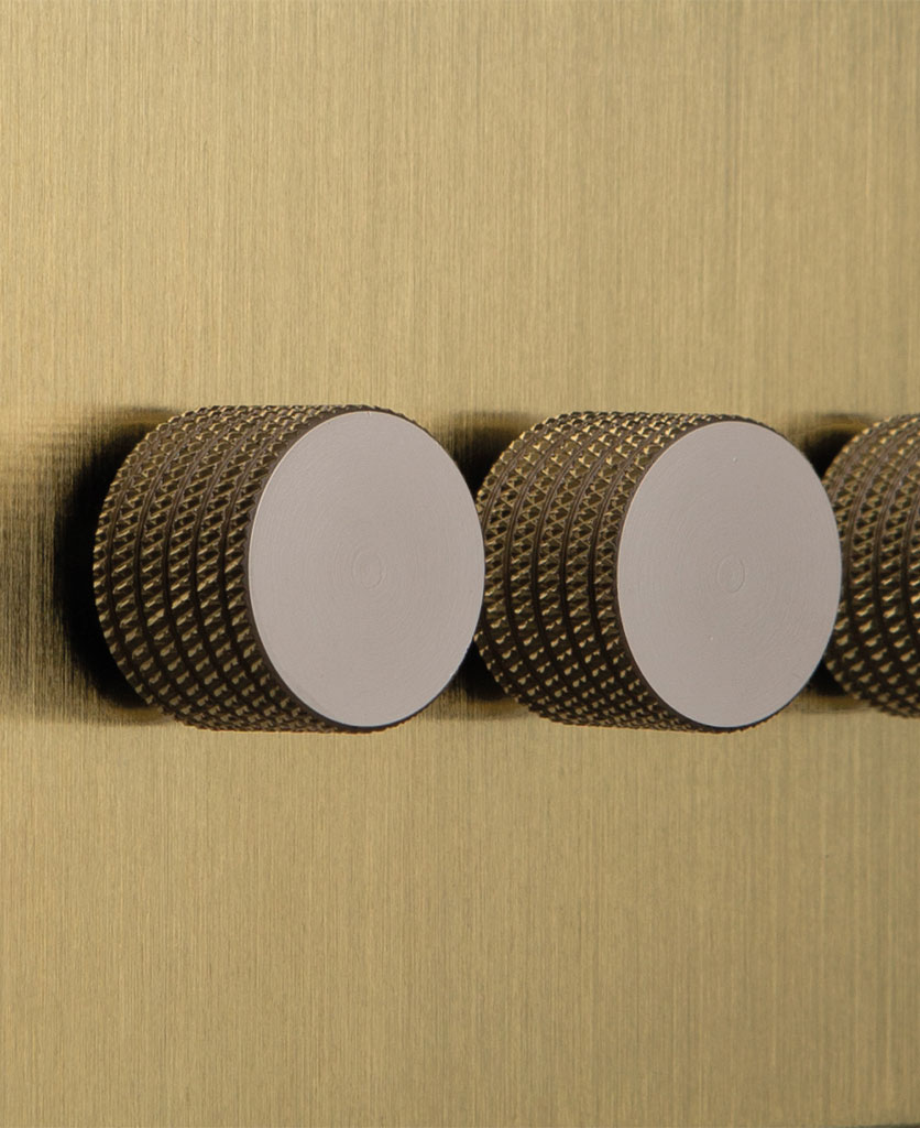 closeup of gold and silver triple dimmer switch