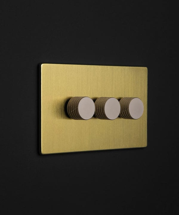 gold backplate with three silver knurled dimmers against black wall