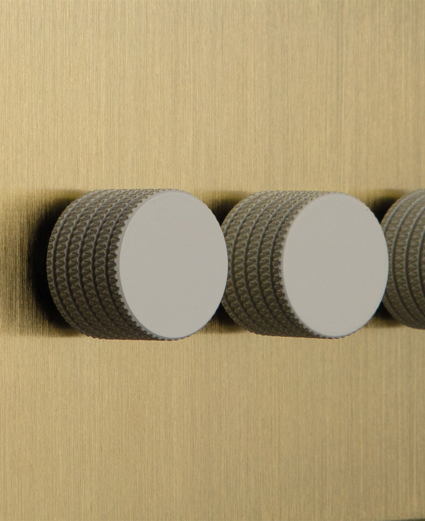 closeup of gold & white triple dimmer switch