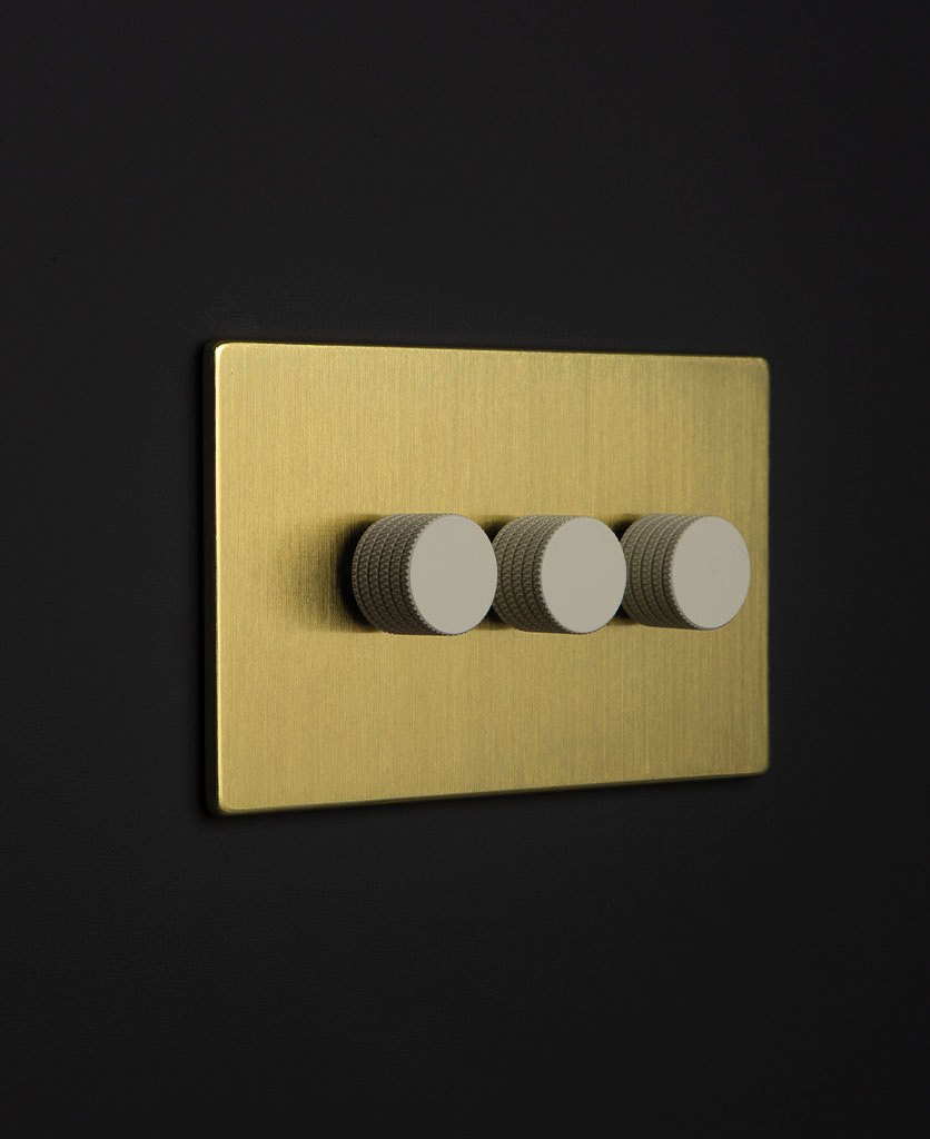 gold backplate with three white knurled dimmers against black wall