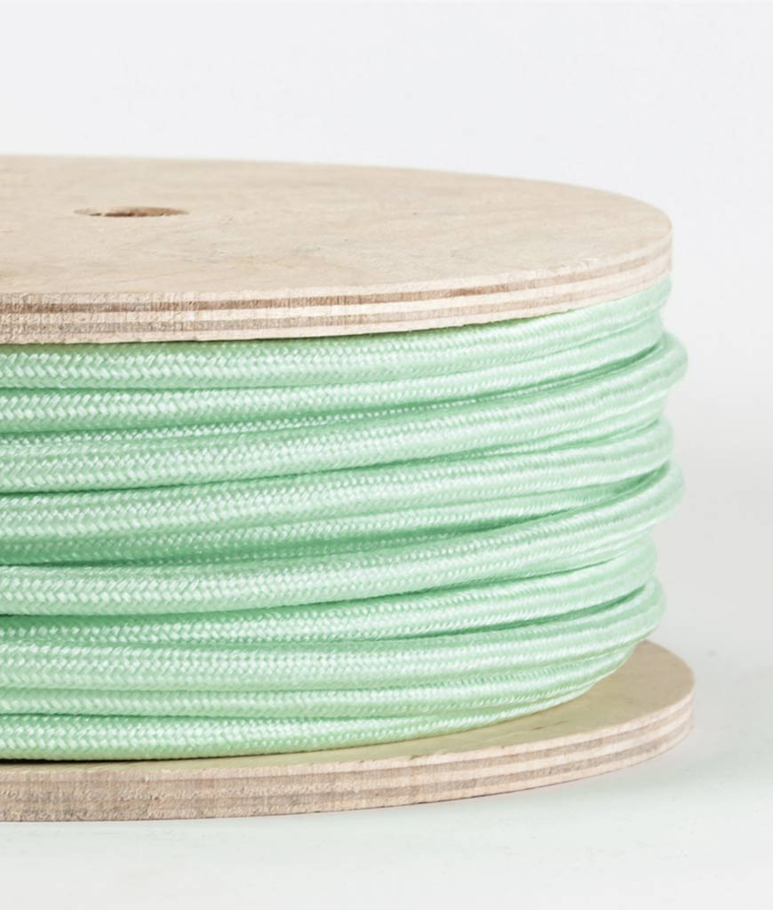 closeup of neo mint fabric cable on reel against white background