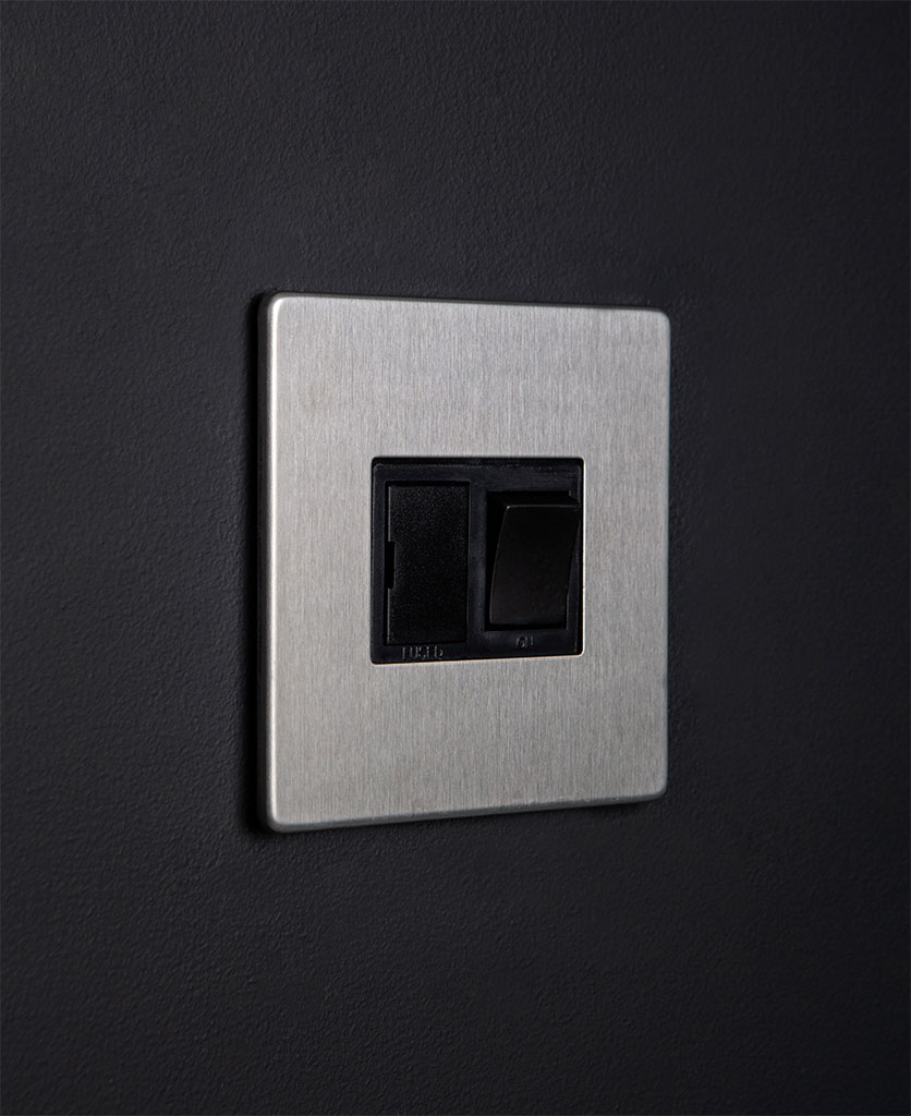 silver fused spur switch with black detail on dark background