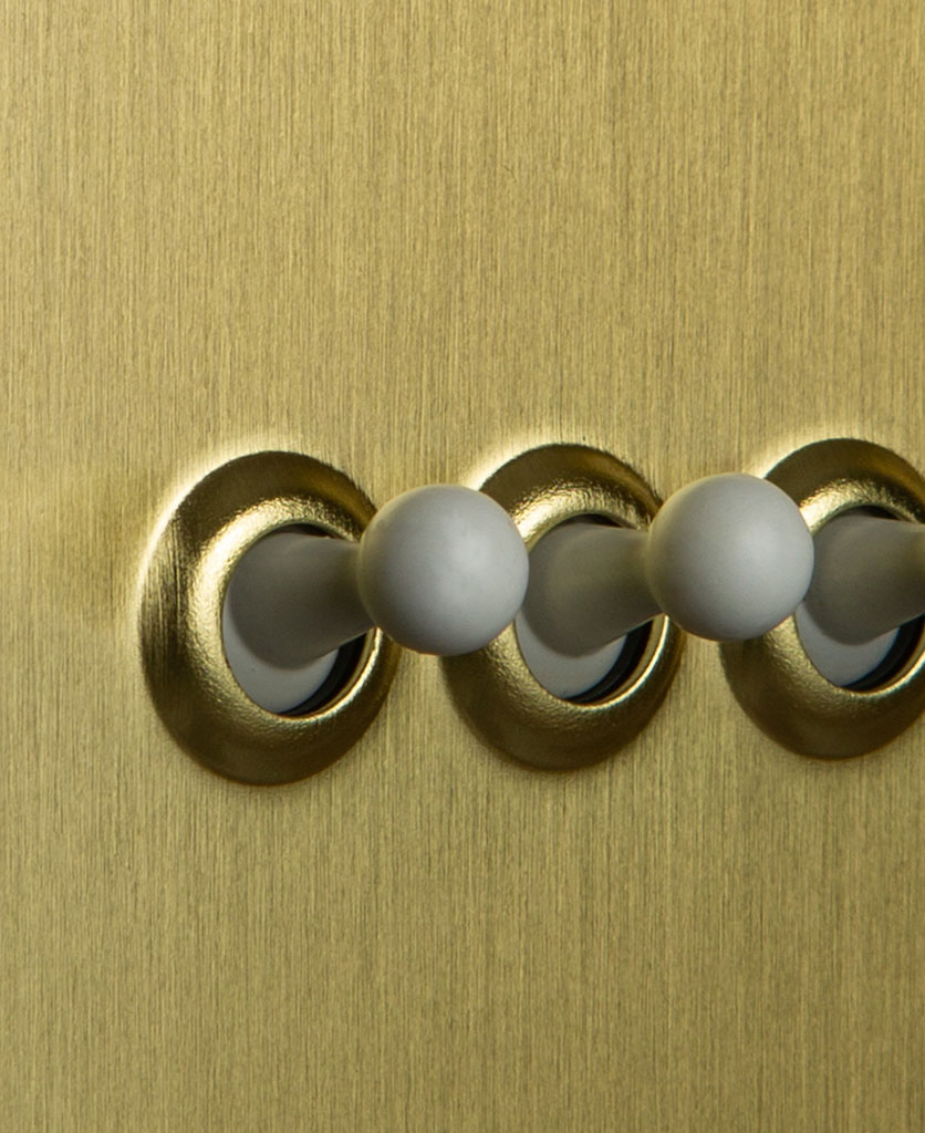 Triple gold toggle switch with white toggles