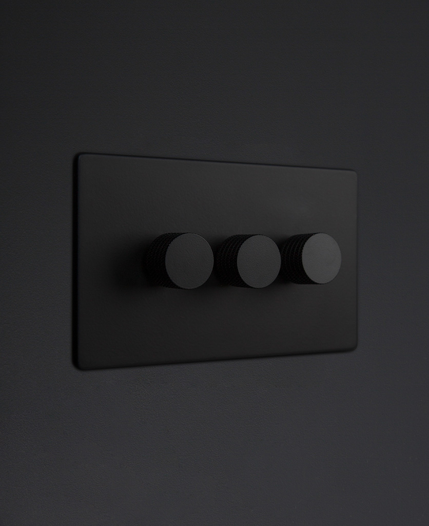 Black three gang dimmer switch with black knobs on black background
