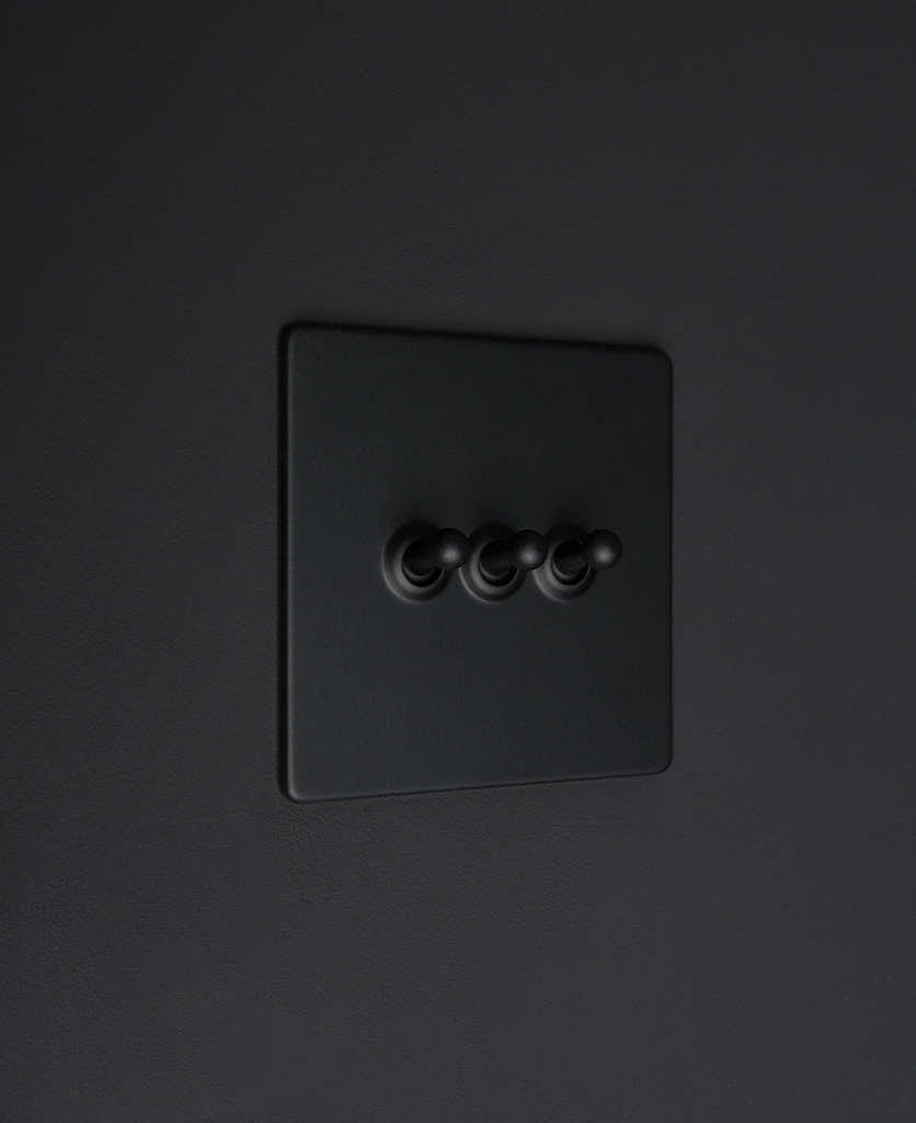 Black three gang toggle switch with black toggles on black background