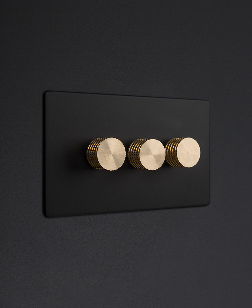 Black three gang dimmer switch with gold knobs on black background