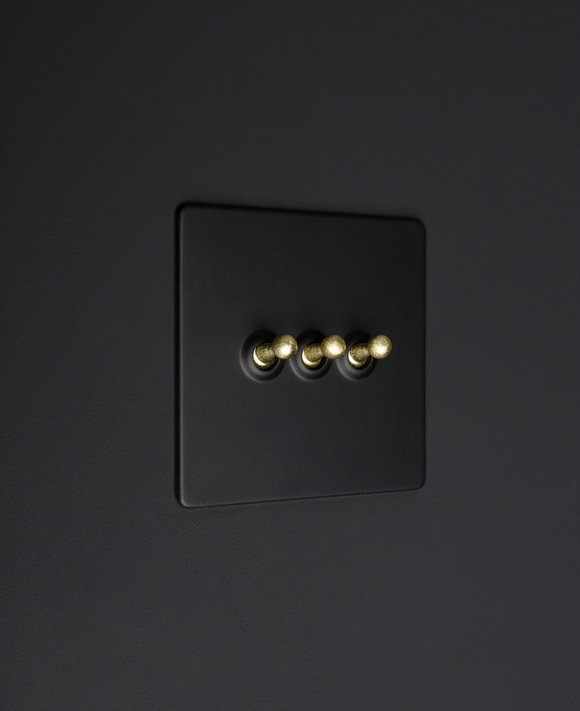 Black three gang toggle switch with gold toggles on black background